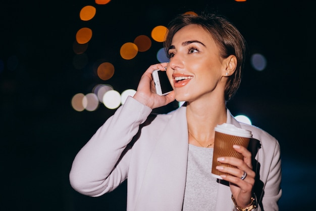Donna parla al telefono e bere caffè fuori in strada di notte
