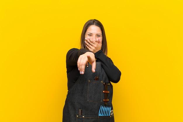 Donna parrucchiere ridendo di te, indicando la fotocamera e prendendo in giro o prendendoti in giro contro l'arancia