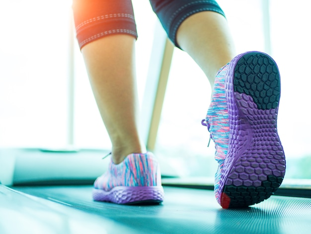 Donna passo e in esecuzione sul tapis roulant in palestra fitness.