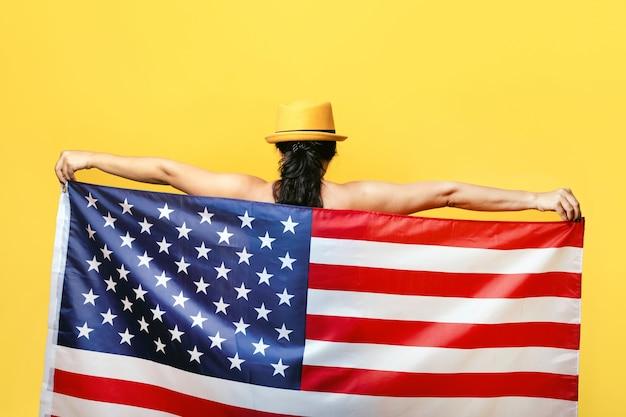 Donna patriottica con bandiera americana. giorno dell'indipendenza degli stati uniti, 4 luglio. concetto di libertà, vista dal retro.