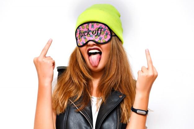 Donna pazza e sfacciata hipster che indossa un cappello al neon e una divertente maschera per gli occhi. stile urbano, lingua fuori. vaffanculo