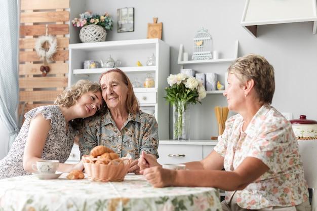 Donna pendente la testa sulla spalla di sua nonna durante la colazione