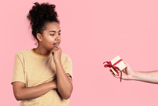 Donna pensierosa che posa mentre ricevendo regalo