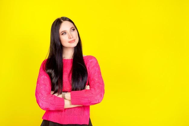 Donna pensierosa su uno sfondo giallo con spazio di copia. sfondi luminosi di concetto per la pubblicità.