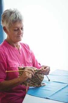 Donna pensionata che fa un po 'di lavoro a maglia