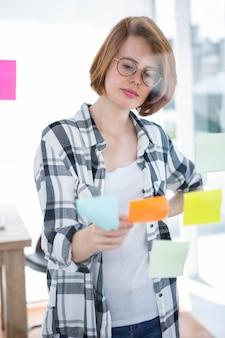 Donna pensosa hipster, seduto alla sua scrivania a leggere le note