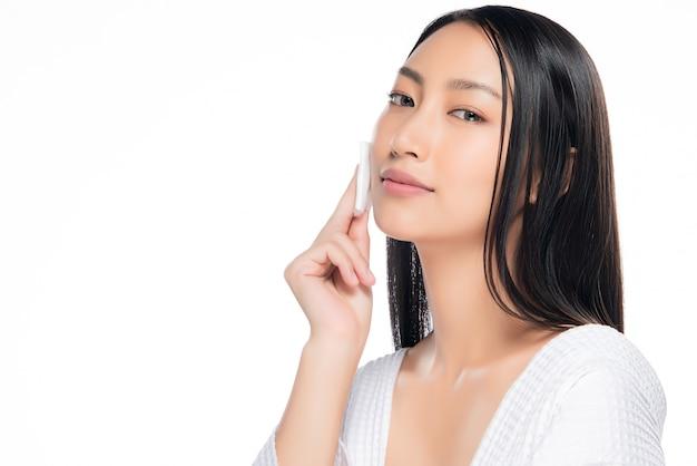 Donna per la cura della pelle che rimuove il trucco del viso con un tampone di cotone.