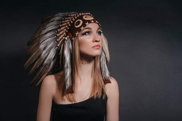 Donna perfetta del ritratto nell'abito degli indiani americani nel fumo su gray