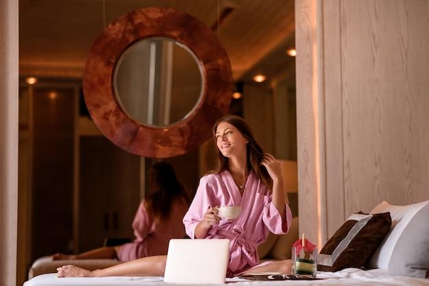 Donna perfetta sorridente in accappatoio rosa con la tazza di tè / caffè e computer portatile che si siedono sul letto nella camera di albergo accogliente.