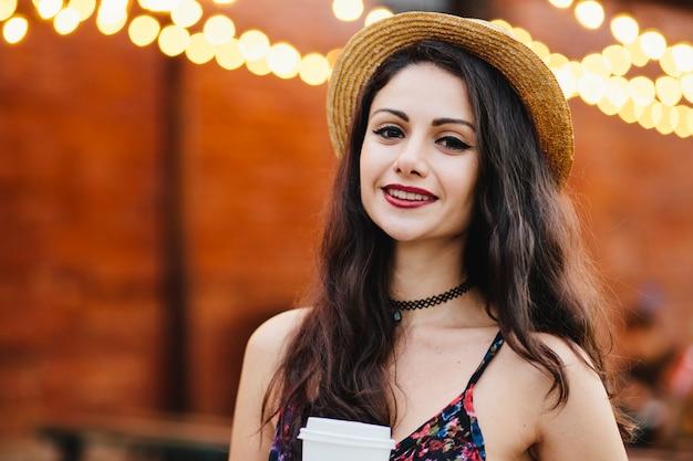 Donna piacevole con capelli neri, occhi lucenti e labbra rosse, con cappello e vestito di paglia
