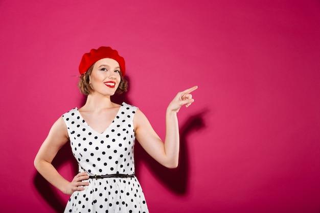 Donna piacevole dello zenzero in vestito con il braccio sull'anca che indica il copyspace e che esamina la macchina fotografica sopra il rosa