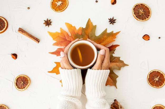 Donna piana di disposizione che tiene una tazza del primo piano del tè