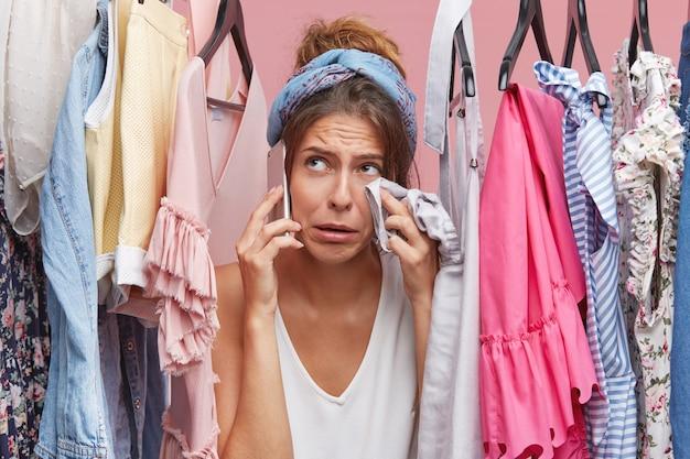 Donna piangente che si pulisce il viso con i vestiti mentre si trova vicino al suo guardaroba, chiamando la sua amica, lamentandosi che non ha niente da indossare e niente soldi per l'acquisto di nuovi abiti. persone, problemi, moda