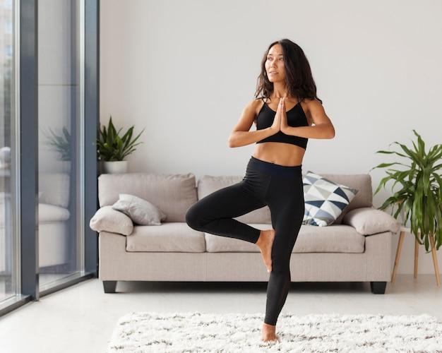 Donna piena del colpo che fa yoga al chiuso