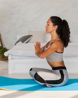 Donna piena del colpo che si esercita sulla stuoia di yoga