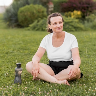 Donna piena del colpo che si siede sull'erba