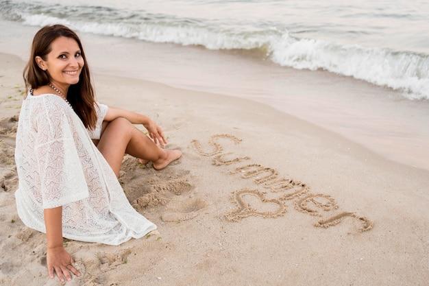 Donna piena del colpo che si siede sulla sabbia