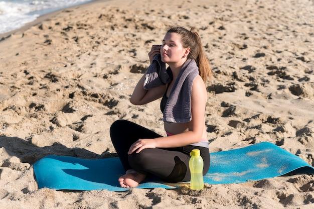 Donna piena del colpo che si siede sulla stuoia di yoga