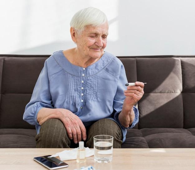 Donna più anziana a casa che controlla termometro