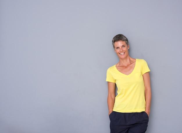 Donna più anziana attraente che sorride contro la priorità bassa grigia