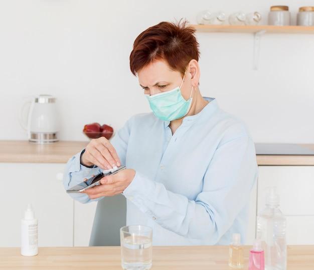 Donna più anziana che disinfetta il suo telefono mentre indossa maschera medica
