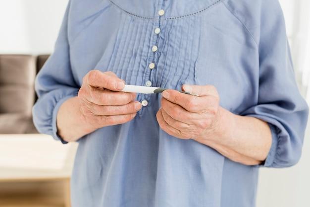 Donna più anziana che esamina termometro
