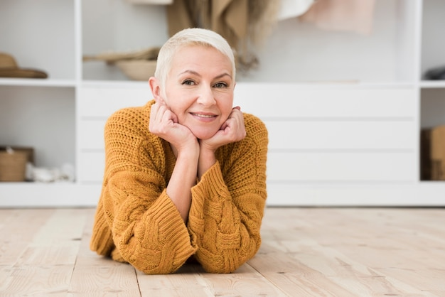 Donna più anziana che sorride e che posa gentilmente