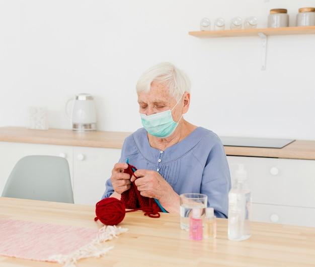 Donna più anziana con la maschera medica che tricotta a casa