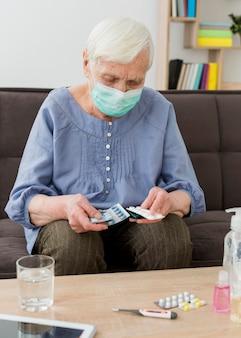 Donna più anziana con la mascherina medica che cattura le sue pillole