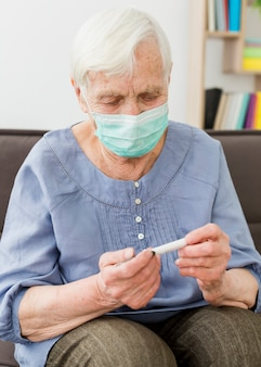 Donna più anziana con la mascherina medica che controlla termometro
