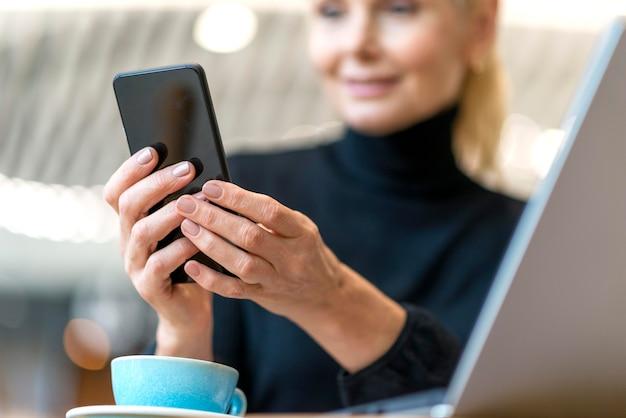 Donna più anziana defocused di affari che lavora al computer portatile e allo smartphone