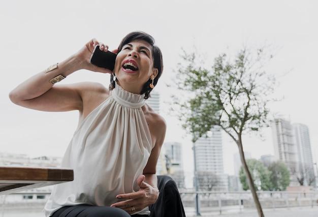 Donna più anziana di smiley che parla al telefono