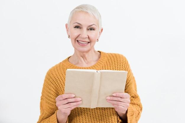 Donna più anziana di smiley che posa mentre tiene libro