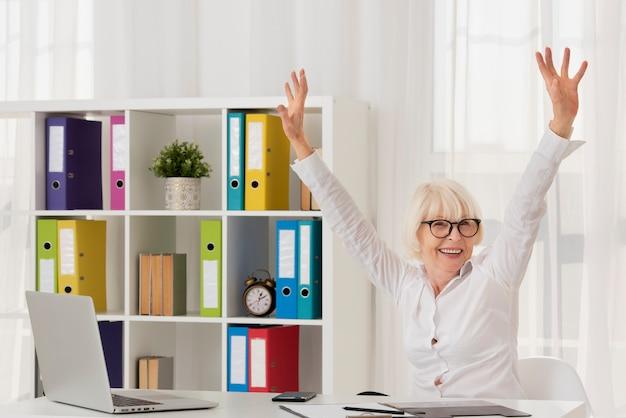 Donna più anziana felice che si siede sul suo ufficio