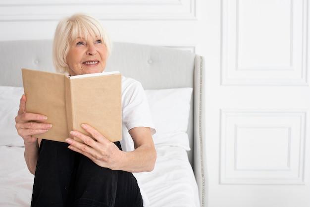 Donna più anziana felice che tiene un libro