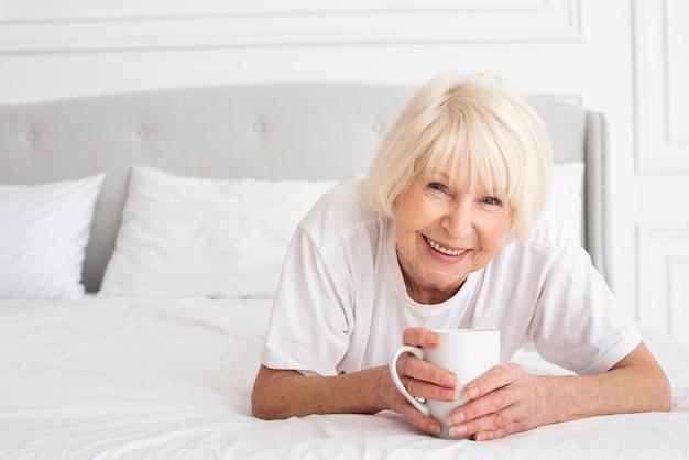 Donna più anziana felice che tiene una tazza