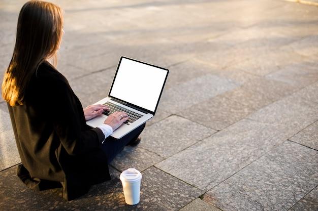 Donna posteriore di vista che per mezzo del computer portatile con lo spazio della copia