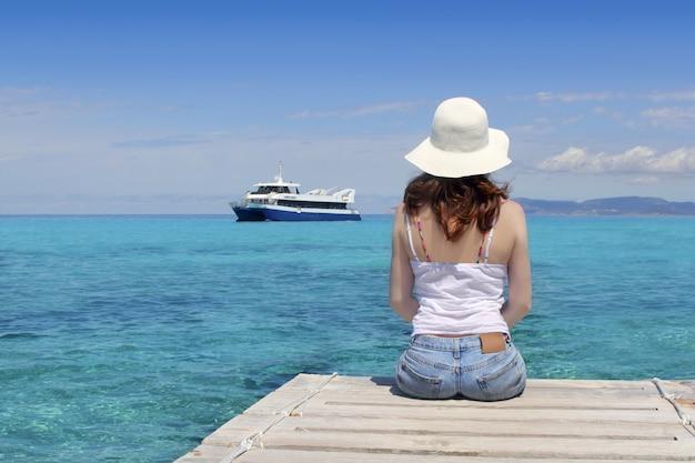 Donna posteriore turistica che osserva il mare del turchese di formentera