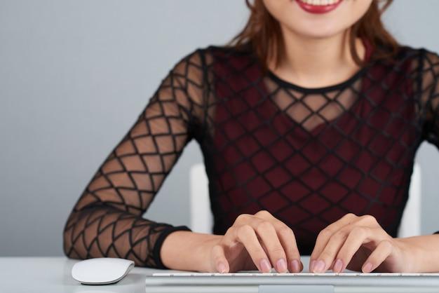 Donna potata impegnata typinh sulla tastiera