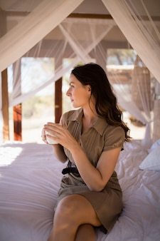 Donna premurosa che mangia una tazza di caffè sul letto a baldacchino