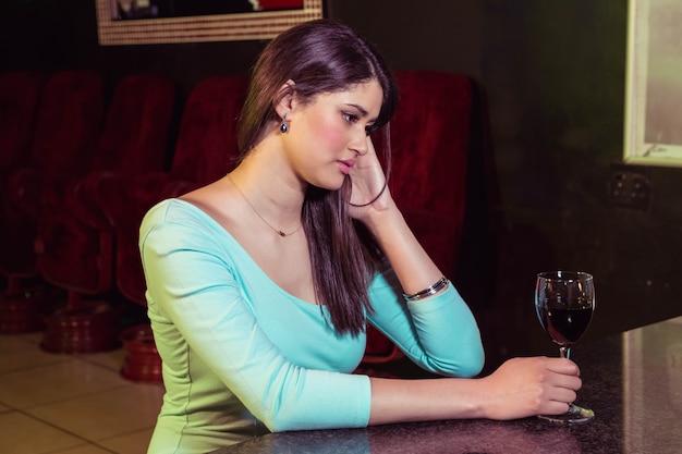 Donna premurosa che mangia vino rosso al contatore della barra nella barra