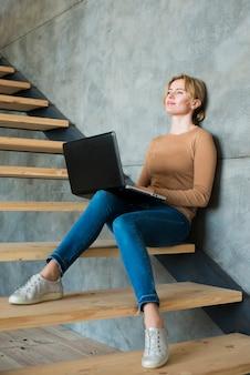 Donna premurosa che per mezzo del computer portatile sulle scale