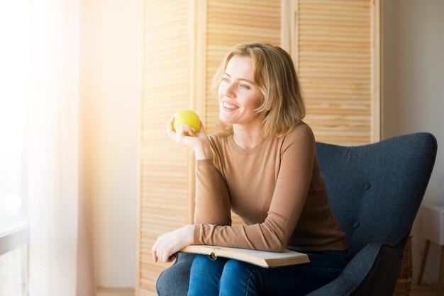 Donna premurosa che si siede con il libro e la mela