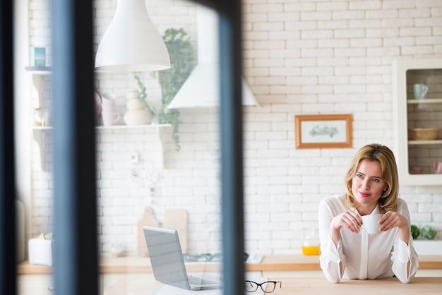 Donna premurosa di affari che si siede con la tazza e il computer portatile di caffè