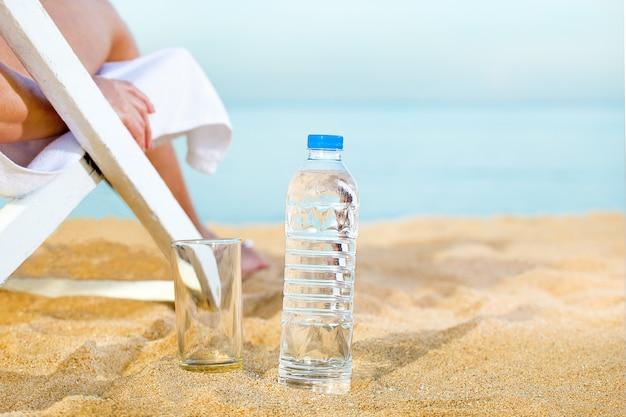 Donna prendente il sole sulla spiaggia e acqua pulita in bottiglia di plastica per sano. acqua potabile sulla sabbia della spiaggia.