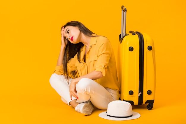 Donna preoccupata che posa accanto ai bagagli e al cappello