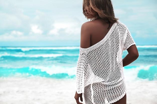 Donna presa il sole in camicetta bianca trasparente che cammina sulla spiaggia di estate