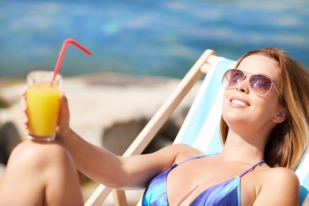 Donna preso il sole con un succo d'arancia