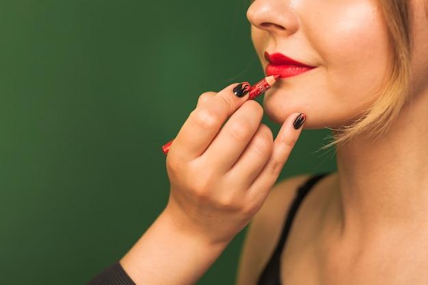Donna professionale che compone le labbra della ragazza
