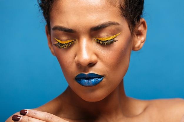 Donna razza mista rilassata alla moda del primo piano con i cosmetici variopinti sul fronte che posa sulla macchina fotografica con gli occhi chiusi, isolata sopra la parete blu